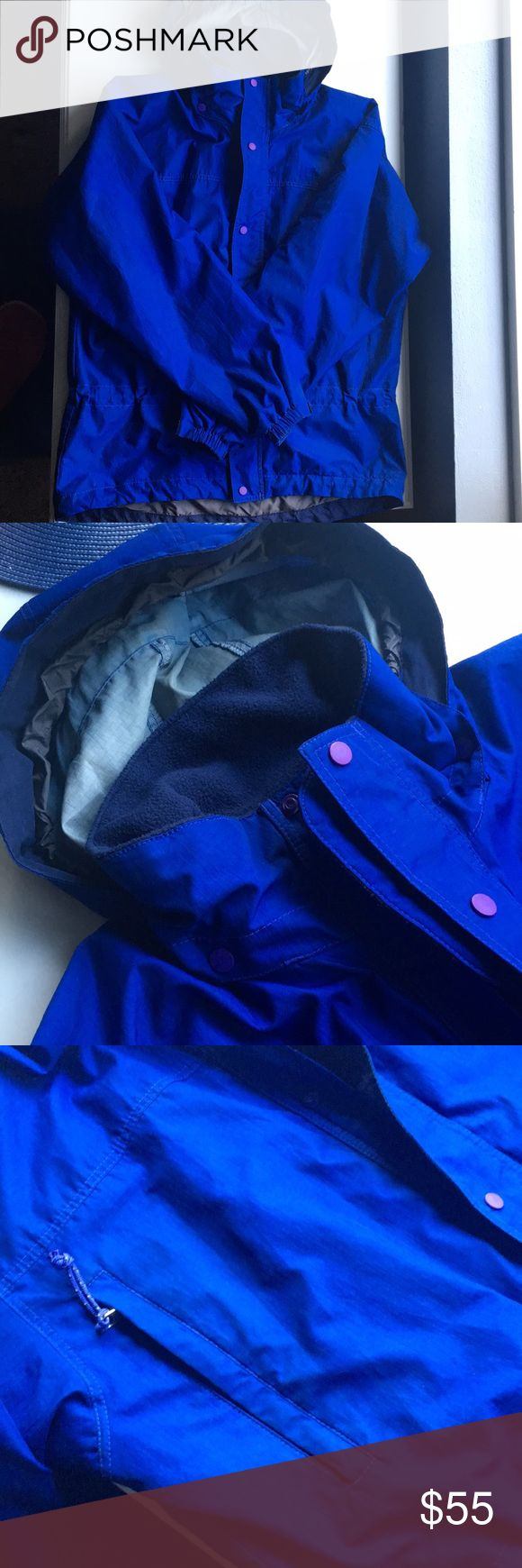 Patagonia rain jacket Older style in great used condition! Bright cobalt blue with purple snap buttons. A waist that can be cinched in from the inside. A hood that can be folded into the collar. Zipper pockets. Velcro at sleeves to make them tighter. Great jacket for those rainy days! No size tag, but definitely a medium! Patagonia Jackets & Coats