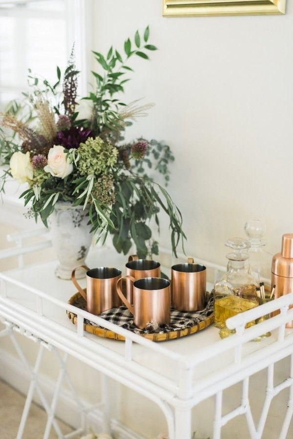 Gorgeous white bar cart topped with copper Moscow mule mugs, a copper cocktail shaker and an arrangement of gorgeous organic eucalyptus greenery and roses. So festive for a holiday party! Love this styling  idea.