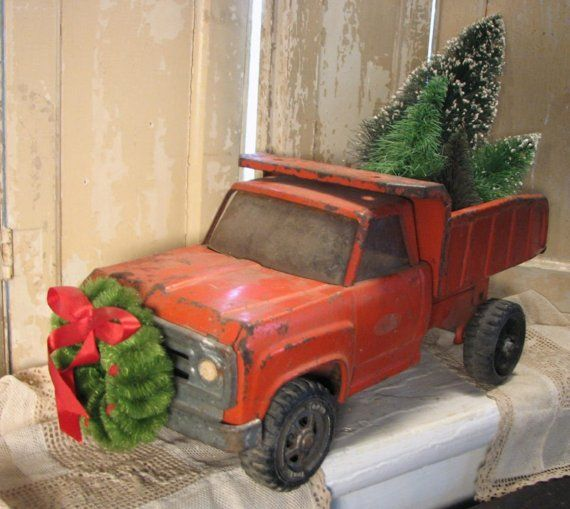 Perfect idea! Old toy truck re-purposed for Christmas with bottle brush trees and wreath.