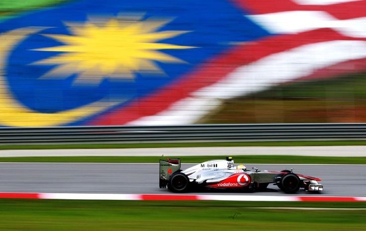 Tradicional foto com a bandeira da Malásia ao fundo