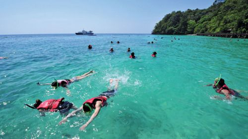 Showing item 1 of 5. snorkelers in crystal clear waters around Pulau Payar