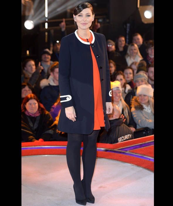 Emma Willis keeps her baby bump warm in this round neck navy coat and red dress