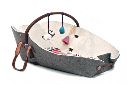 Xai is a play mat for babies that can be transformed into a bassinet or baby hammock. It incorporates a wool mattress and a wooden arch for hanging baby toys.