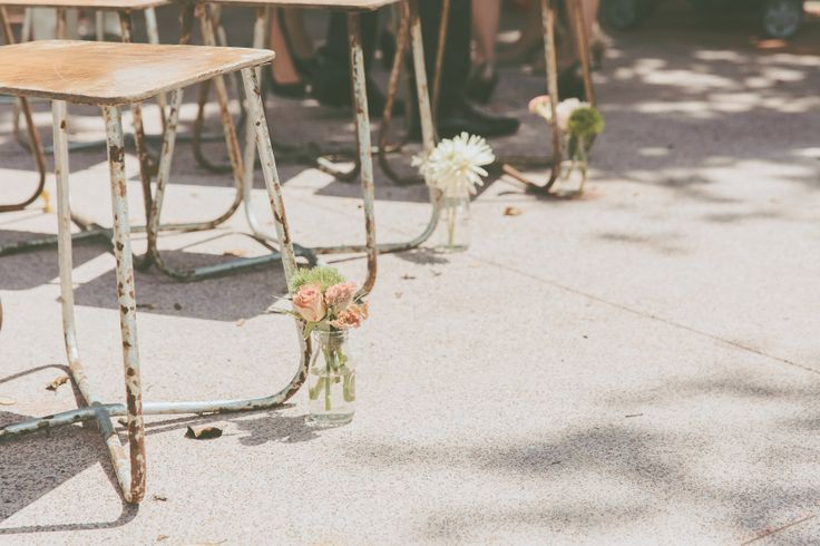 aisle created out of vintage stools and little jars  with fresh blooms