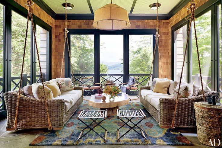 The sleeping porch of this Thom Filicia–decorated family retreat in New York's Adirondack Mountains includes a slate-color throw he designed for Eastern Accents and a carpet for Safavieh, also of his design.