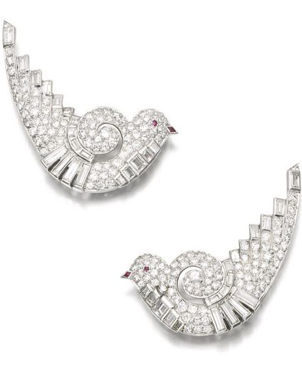 PAIR OF DIAMOND EAR CLIPS/BROOCHES, 1930S Each designed as a stylized dove set with circular-cut and baguette diamonds, the eyes and beaks set with polished rubies.