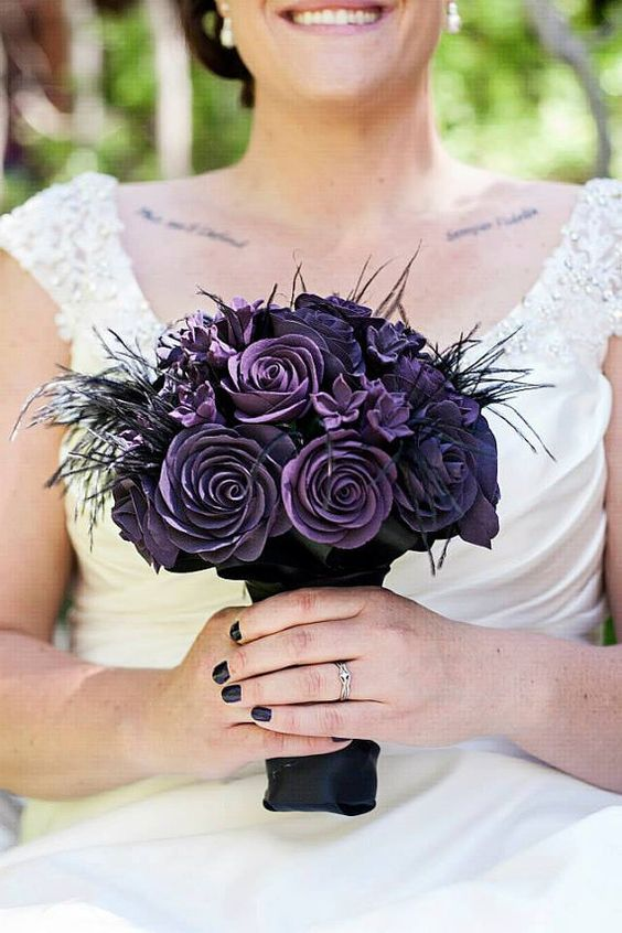 Wedding bouquet of purple flax flowers, with black twig and feather ...
