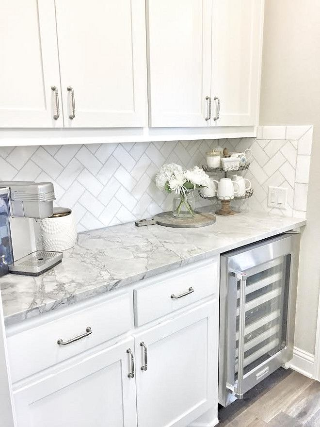Small butlers pantry with herringbone backsplash tile and white…