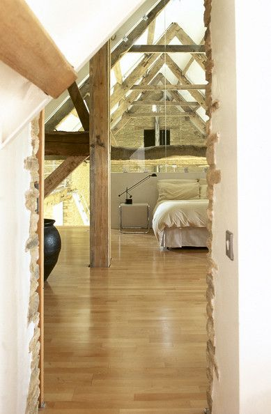Loft bedroom in a converted barn with a wood floor, exposed roof trusses, contemporary lighting