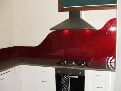 Red Curved Kitchen Splashback - This red splashback has been curved to add a little more style. It features a running waterhole and some sit...