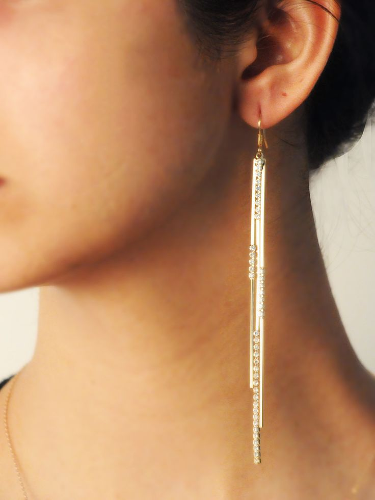 Celia Diamonte Drops -  INR 1,499 -  These statement earrings features long metal strips that are partially set with crystals. The slender but long drops are finished in a Gold metal and look great on all as they elongate your frame.
