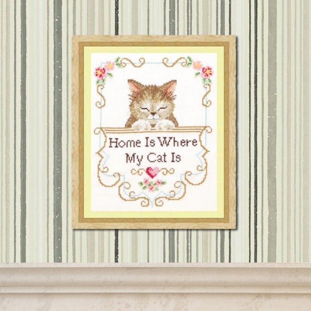 """An extremely cute and contented cat peeps out at you. He is surrounded by an elagant floral and scrollwork frame and below are the words """" Home is Where my Cat is"""". This unusual gift is sure to warm the heart of any cat lover.  Worked on ivory linen with gorgeously shaded cotton, this enchanting sampler is very eye-catching."""