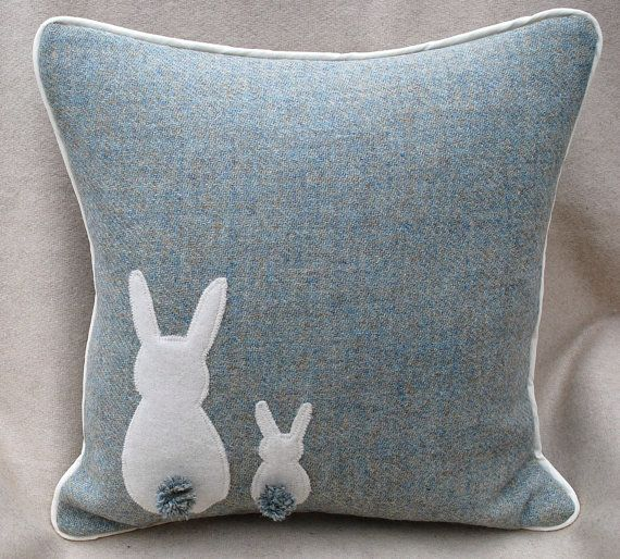 HARRIS TWEED BUNNY CUSHION  This Beautiful Harris Tweed Bunny Cushion is made from duck egg blue tweed which is a refreshing colour to bring in the spring and summer. It is a great Easter theme but will also take you through the spring summer. The bunnies tails have been hand made out of matching isle of harris spun wool ... Chosen to match the tweed fabric. It measures approx. 16 x 16 and comes complete with a feather inner for that luxurious feel.  It carries the Harris Tweed Label which…