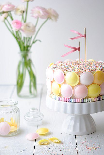 Pretty pastel cake decorated with flying Look-O-Look saucer candy, candy necklaces, and sprinkles.