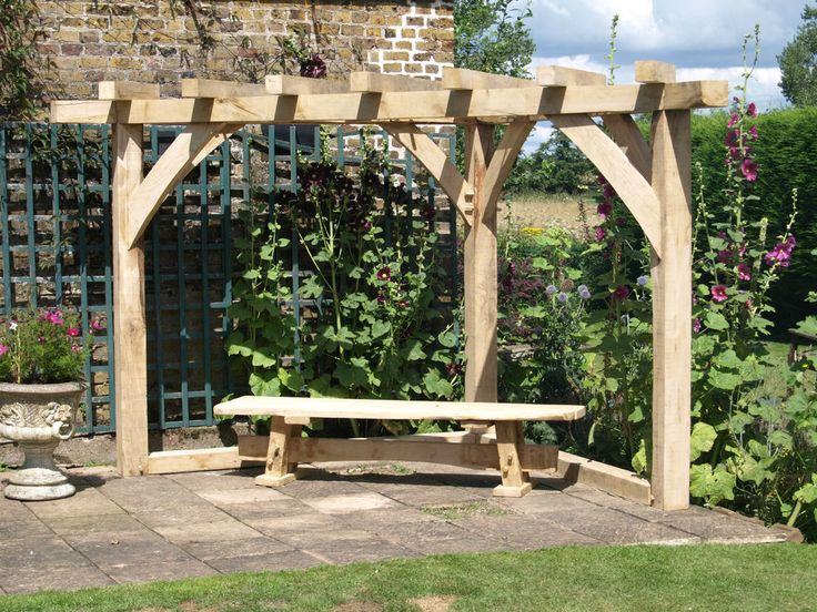 Hand built corner kit form pergola in green oak. Traditional joinery allowing tapered seasoned oak pegs to draw dowel joints tight. Joists and compound front brace hex screw and oak plugged. Footprint 2400mm x 2400mm x 3500mm.