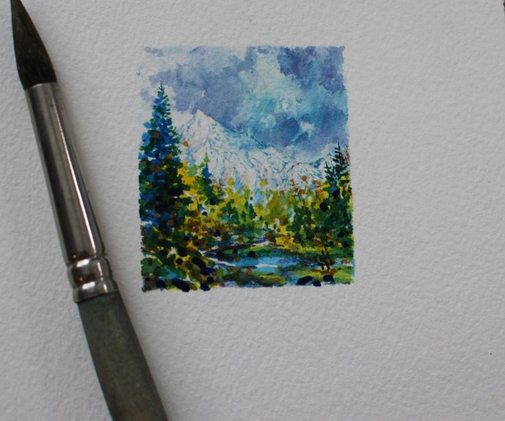 "Mount Everett, BC. A Series of Miniatures Number 3. A Glimpse into my World. 1.5"" X 1.75"", Watercolour, Matted.  I put a paintbrush beside the painting to show the scale."
