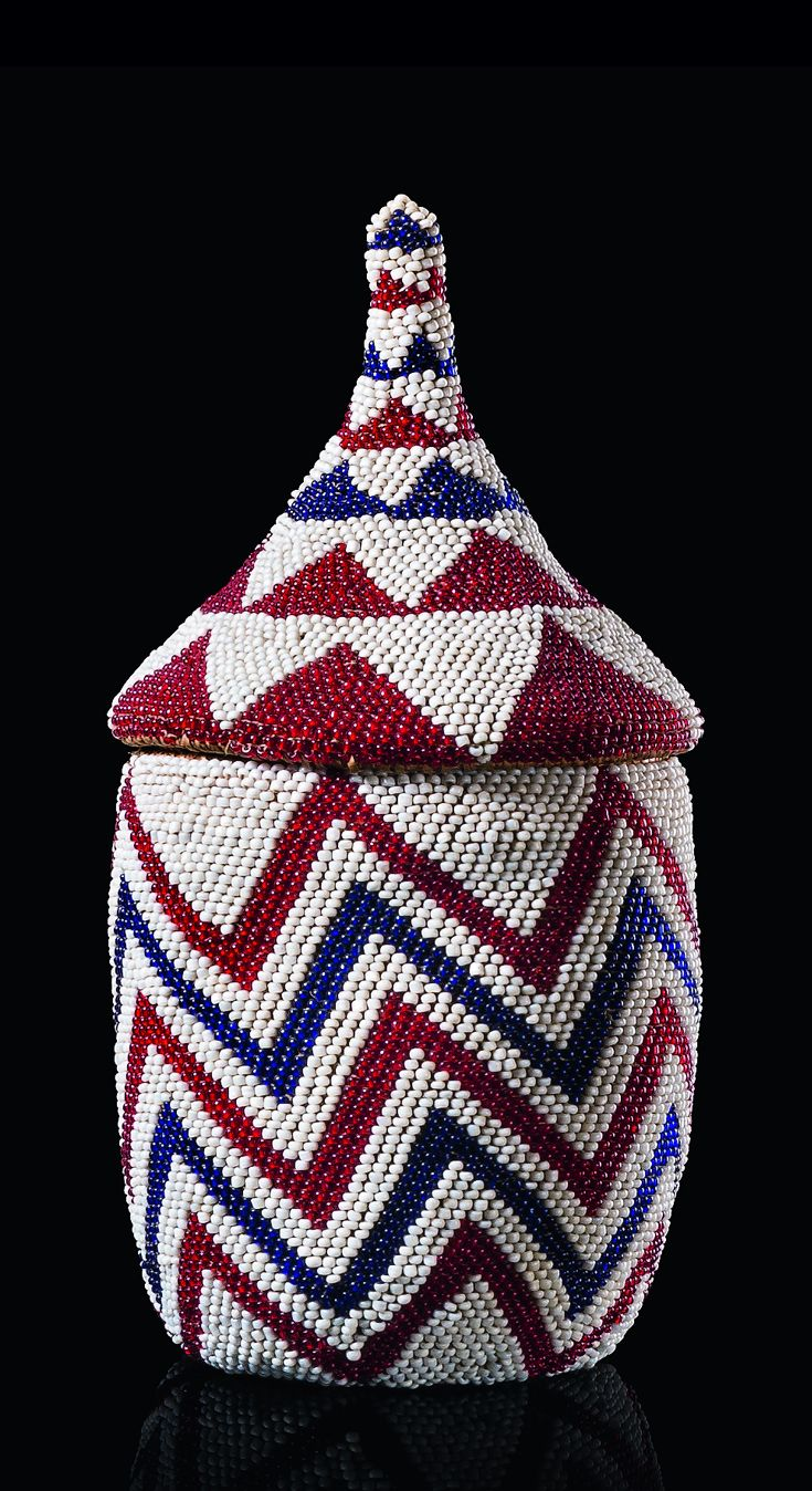 Africa   Beaded basket with lid ~ 'igeseke' ~ from the Tutsi people of Rwanda   Straw basketry, coated with a delicate weave of red and white miniature glass beads, forming triangular and striped patterns, hat-shaped lid with elongated handle