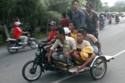 Acehnese males journey on a motorized pedicab while they leave to improve ground after having a robust earth quake had been felt within Banda...