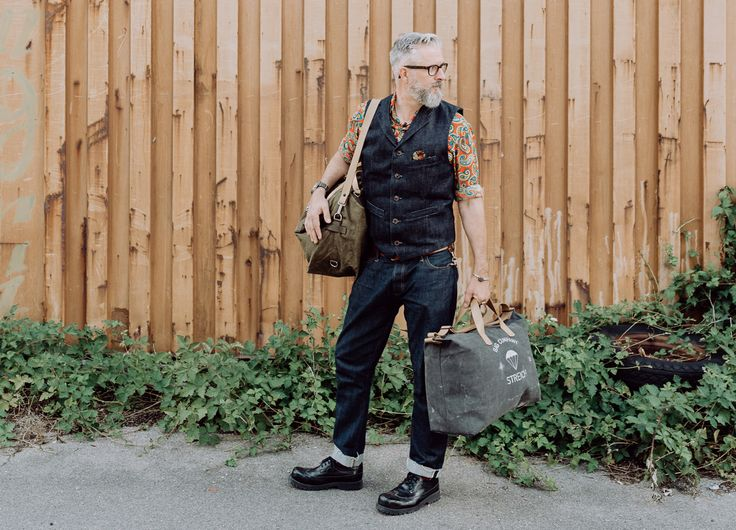 The designer Bruno Streich with the SOHO bag and The KALAMATA bag. both nade out of vintage swiss army tent canvas and gunbelts. He wears a selvedge denim waistcoat by STREICH. #streichbag #brunostreich #bag #travelbag #weekenderbag #armystyle #gymbag #accessories #beardmodel #beard #gentlemanstyle #saltandpepper