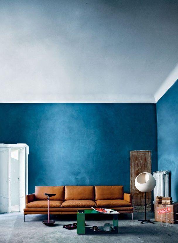 Sofá de couro marrom com parede azul