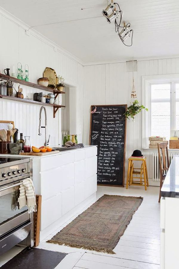 White kitchen walls, painted floor, open shelving, accessories and staging on the shelves. Also love the giant chalkboard.