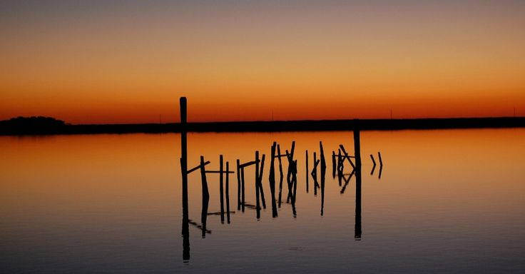 O pôr do sol cria uma espécie de caligrafia em um velho píer. Ocupada pelos colonizadores ingleses no século 17, a Smith Island, na Baía de Chesapeake, está desaparecendo em decorrência do aquecimento global e o aumento do nível do mar, em Maryland, EUA
