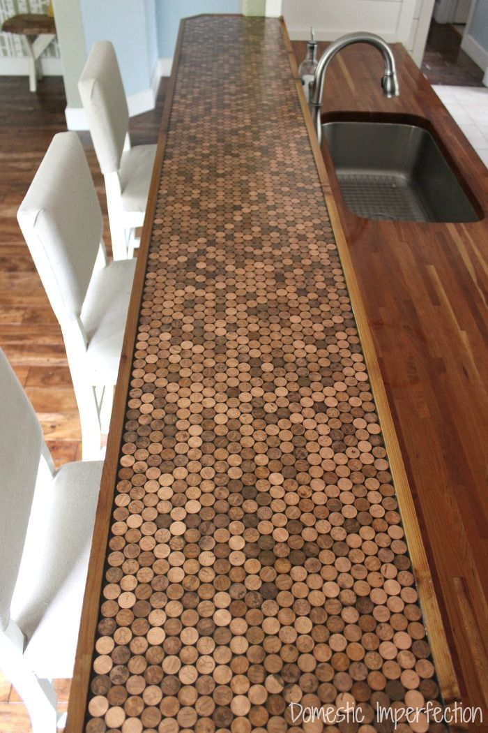 Last September we finished our butcher block countertops, but we didn't do our bar area. I mentioned in that post that I was open to suggestions and got the great idea to cover it in pennies and ep...
