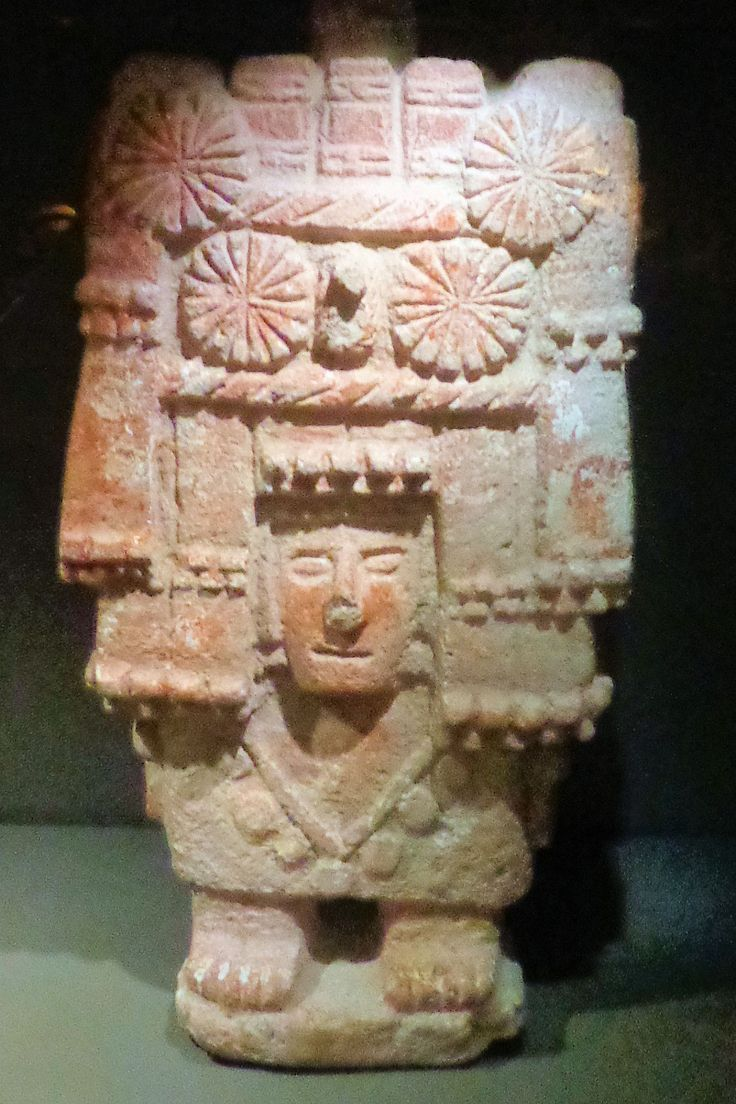 Stenen beeld van de godin van de maïs van de Azteken uit het centraal hoogland van Mexico, vervaardigd rond het jaar 1400. Haar hoofdtooi stelt een tempel of maïsschuur voor. De rozetten zijn papieren bloemen die als offers dienden.