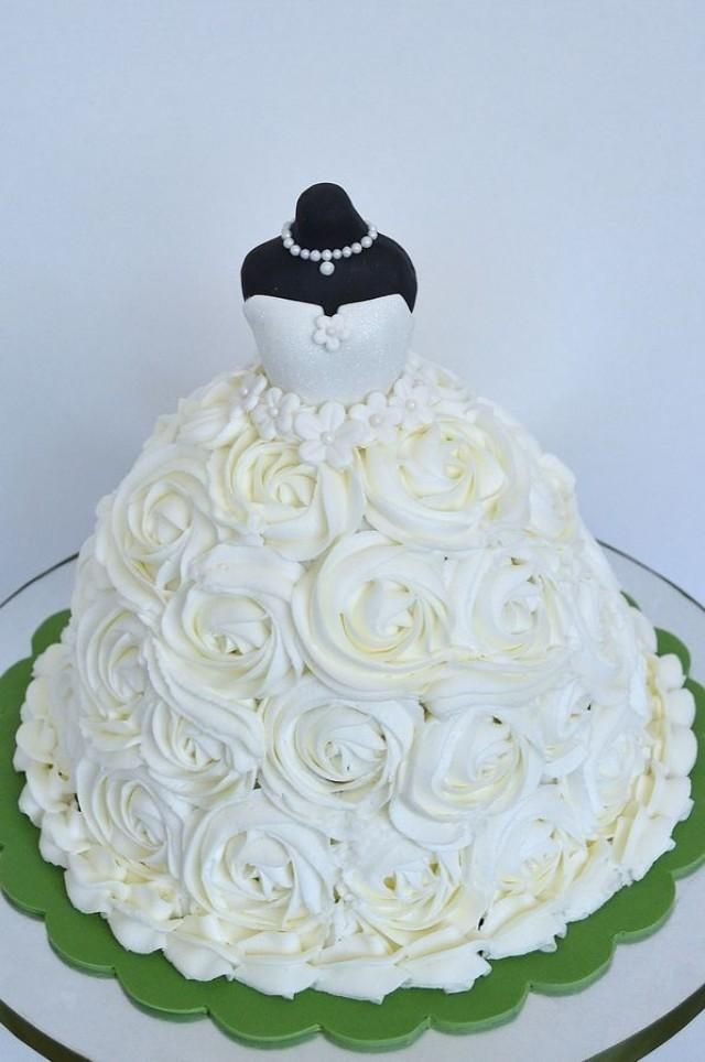 Weddbook ♥ This wedding cake is completely decorated with ivory roses. There is a black woman dummy wearing white dress with white necklace at the top of the cake, this looks adorable and stylish. Your guests will be amazed to see such a beautiful cake.