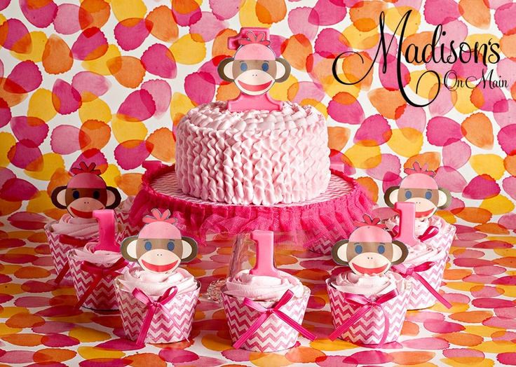 I made this smash cake and 30 cupcakes for a little girls 1st birthday.  Embers Aunt wanted her to have a sock monkey theme.  I made the custom wrappers, then created edible monkey faces and 1s out of ghirardelli melting bars I dyed hot pink.  Smashy has a large 1 with an edible face as well.  All of it is french vanilla with white chocolate mousse filling and raspberry sauce.  Photo by Kevin Paul Photography
