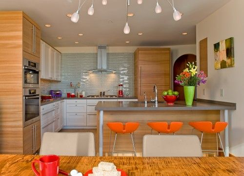 contemporary kitchen, love the pop of color with the orange stools and accessories. the kitchen is so neutral you can easily change out the look with new stools, etc. I like the blue glass tile backsplash, the combo of enameled cabinets with wood, and the funky light fixture.