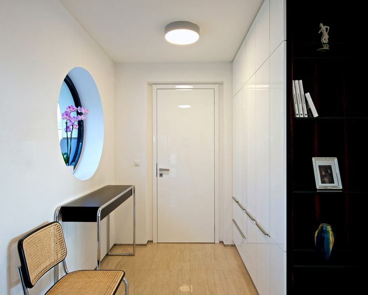 Add white high gloss lacquered wardrobes to an entryway to provide additional storage and closet space by Hans Krug Fine European Cabinetry