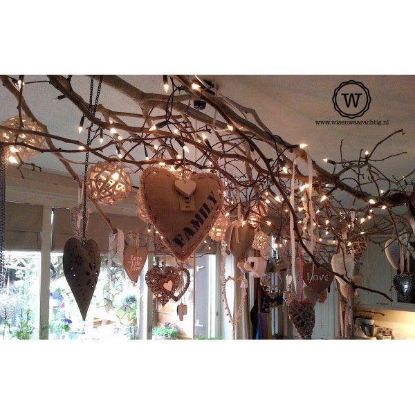 Sfeerfoto: houten harten en jute hart met persoonlijke tekst aan een mooie tak boven de tafel - Wis en Waarachtig