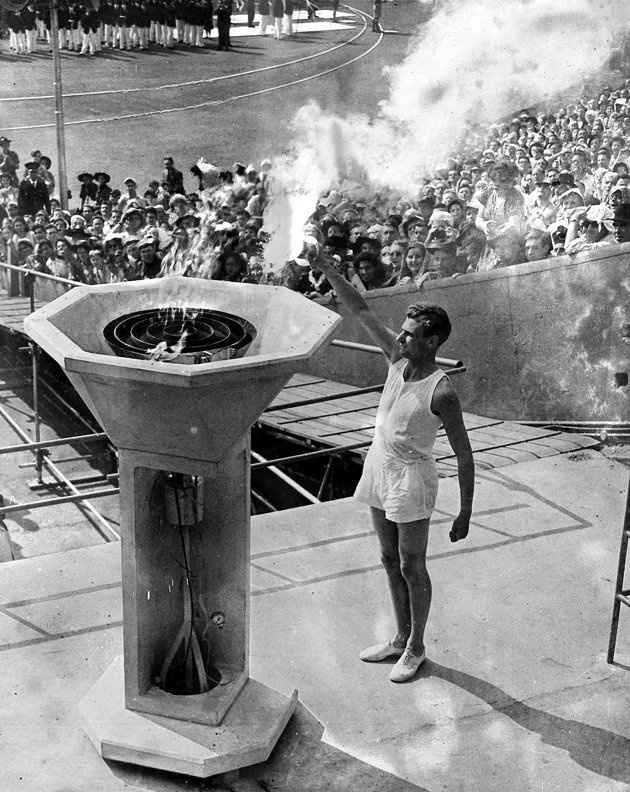 Olympic Opening Ceremonies British athlete John Mark lights the Olympic Flame from the Olympic torch during the opening ceremony of the 1948 London Olympics in Wembley Stadium, London, July 29, 1948. (AP Photo)-