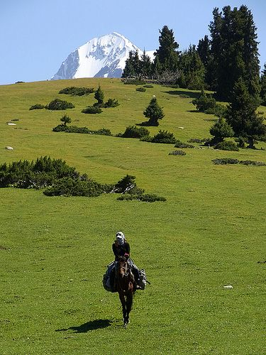 Horse trekking in the Tien Shan Mountains, Kyrgyzstan. The Tien Shan, is a large system of mountain ranges located in Central Asia. The highest peak is Victory Peak at 7,439 metres. The range is on the border between China and Kyrgyzstan.