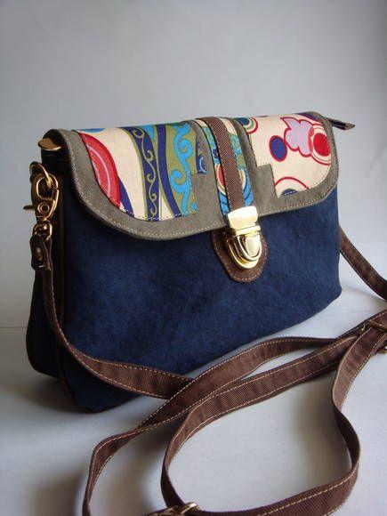 Esta bolsa possui divisória e alça removível. Pode se transformar em carteira, bolsa de ombro ou transversal. Ela é feita de lona estonada e detalhe da tampa em tecido de algodão. R$ 95,00