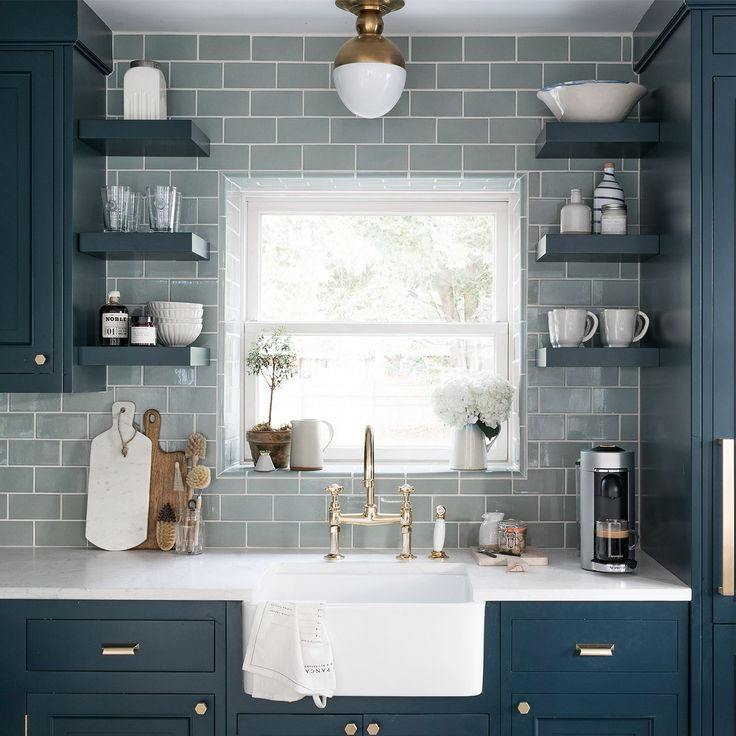 Our Beach House Kitchen: The Reveal - check out this kitchen inspiration from our New York kitchen with two tone cabinets the first color is a navy blue with brass hardware (file box pulls) and brass vintage style faucets with farmhouse sink. The green grey subway tile with white grout pair perfectly with the open shelves.