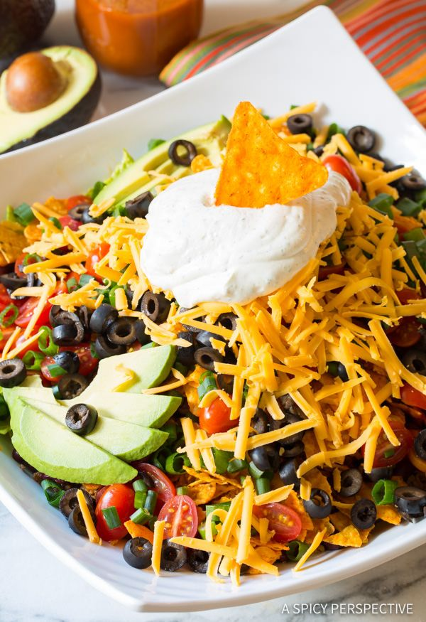 Ultimate Dorito Taco Salad Recipe - An All-American version of classic taco salad with layers and layers of texture and zesty flavor. This is a must-make fo