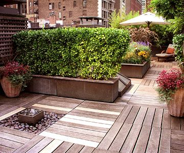 """Modern Design: The deck is covered with ipe-wood planks set in a checkerboard pattern for a modern look. The decking """"floats"""" over the roof to comply with the roof warranty. Tall plants occupy planter boxes wrapped in crimped copper sheeting, dividing the box-shape space into the activity cent"""