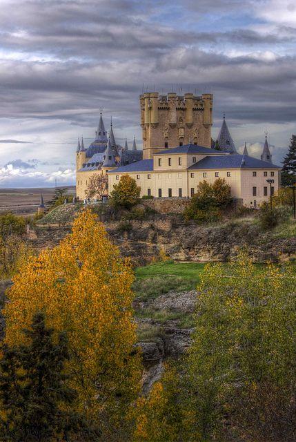 CASTLES OF SPAIN - Alcázar de Segovia, se alza sobre un cerro en la confluencia de los   ríos Eresma y Clamores. El Alcázar fue construido originalmente como una fortaleza, también como   un palacio real. Se supone que en tiempos de la dominación romana de la ciudad ya hubo un castro o   fortificación. Sobre los restos de éste, fue erigido una fortaleza árabe. La primera noticia documental   data del año 1122, poco después de que Alfonso VI de León reconquistara la ciudad.