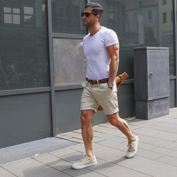 Comprar ropa de este look: https://lookastic.es/moda-hombre/looks/camiseta-con-cuello-circular-pantalones-cortos-zapatillas-plimsoll/20252 — Camiseta con Cuello Circular Blanca — Gafas de Sol Negras — Correa de Cuero Marrón Oscuro — Pantalones Cortos Beige — Zapatillas Plimsoll en Beige
