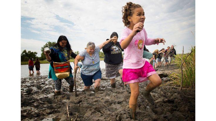 sabella Flannery (9) van Kansas City, Missouri, pakt haar weg door diepe modder na het bidden met haar moeder, Stella, en andere vrouwen aan de oevers van de rivier de kanonskogel in de buurt van camp. Isabella en Stella kwam naar Noord-Dakota uit bezorgdheid dat als een ongeval zich voordoet en de pijpleiding ruwe lekkages in de Missouri-rivier, het niet alleen permanent Rock's watervoorziening vervuilen zal, maar ook hun eigen en die van vele anderen die stroomafwaarts wonen.