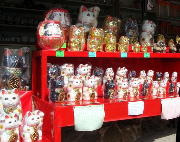 """Figurines of the """"beckoning cat"""", also known as lucky cat, or fortune cat (known in Japan as """"'maneki-neko""""), are sold to the faithful in shops outside Fushimi Inari. Maneki-nekos are a common Japanese lucky charm, which can bring benefits to the owner. The figurine is usually made of ceramic, with a decoration around the neck, adorned with coins or food items, and holding up a paw. White cats are for good luck, black cats for good health, and gold cats bring monetary wealth."""