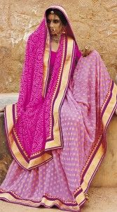 Rajasthani Bandhej Saree is crafted with a exclusive designer printed work all over, embroidery work in the horizontal panel and contrast on the border. Bandhej Sarees with Gota work are most popular in Rajasthan and Gujarat. This Rajwada Fashion saree comes with matching blouse piece.The blouse of this saree can be stitched in the maximum bust size of 42 inches...