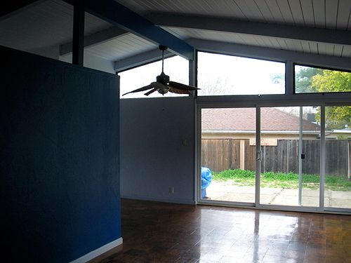 empty mid-century living room with open beam ceiling and sliding glass doors