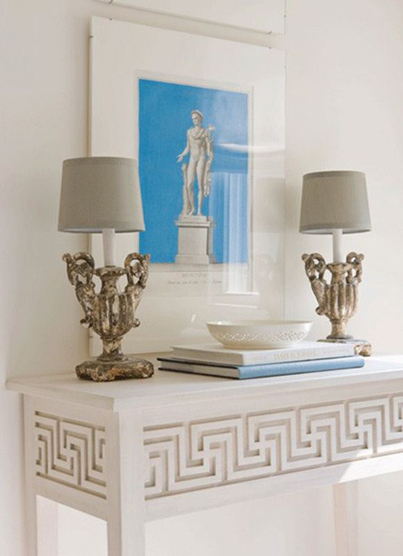 A carved Greek Key table & matching vintage lamps add style to a foyer.