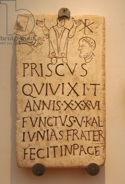 "Italy. Roman funerary stele of Prisco.  4th century AD. Early Christians. Inscription: Christian phrase appears ""in pace"". The symbol of the dove and the olive branch and the monogram of Constantine T. 4th century AD. Baths of Diocletian, part of the National Roman Museum Rome. Italy."