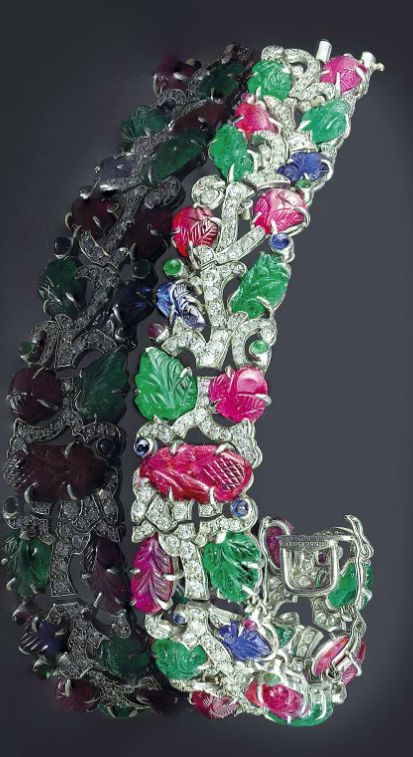AN IMPORTANT MULTI-GEM AND DIAMOND 'TUTTI-FRUTTI' BRACELET, BY CARTIER  The pavé-set diamond branch enhanced by carved ruby, emerald and sapphire leaves, with cabochon detail, circa 1928, 18.0 cm, in red leather Cartier case Signed Cartier, no. 2919264 and 9677