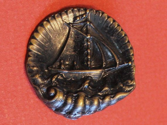 Antique Tinted Brass Picture Button of Sailing Ship in a Shell - Lovely detail with lots going on - beautiful one piece high relief stamped brass button. Loop Shank. Measures 1 & 1/2 at center. Beautiful Old Button In Excellent Condition. I ship world wide with the exception of Italy & Spain - For Buyers outside Canada & Continental USA please send your zip or postal code for actual shipping cost and shipping options. Always happy to combine shipping. Thanks for stopping by.