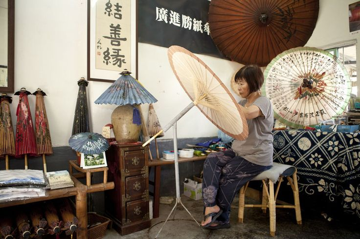 Woman pasting cotton paper onto the edge of an oil paper umbrella